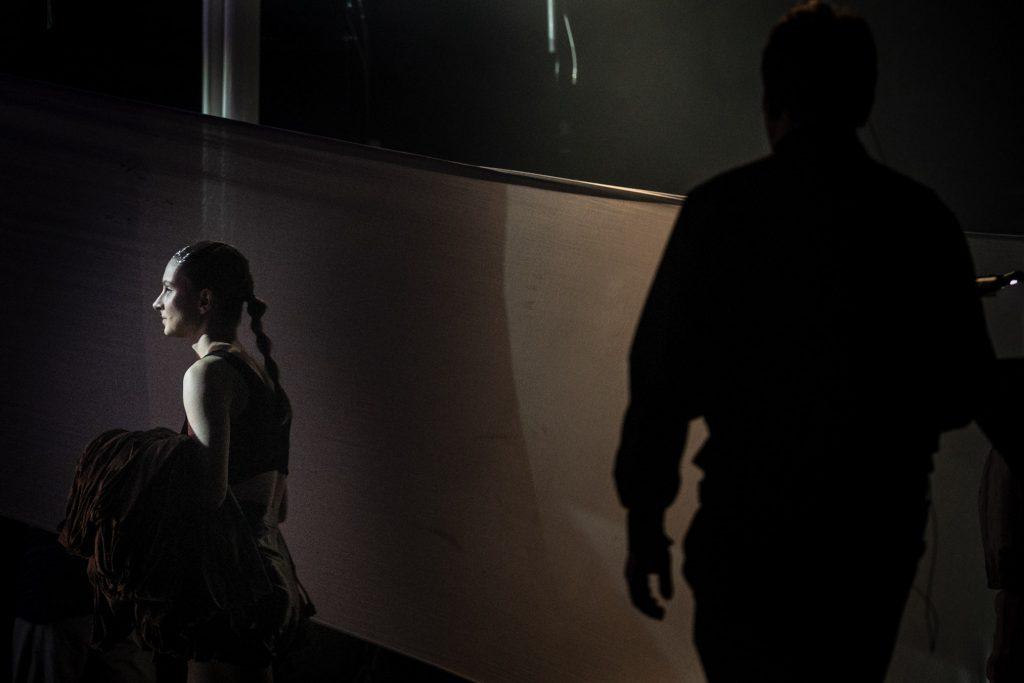 W lewym rogu siedzi kobieta patrząc przed siebie. Po prawej stronie widoczny zarys mężczyzny.