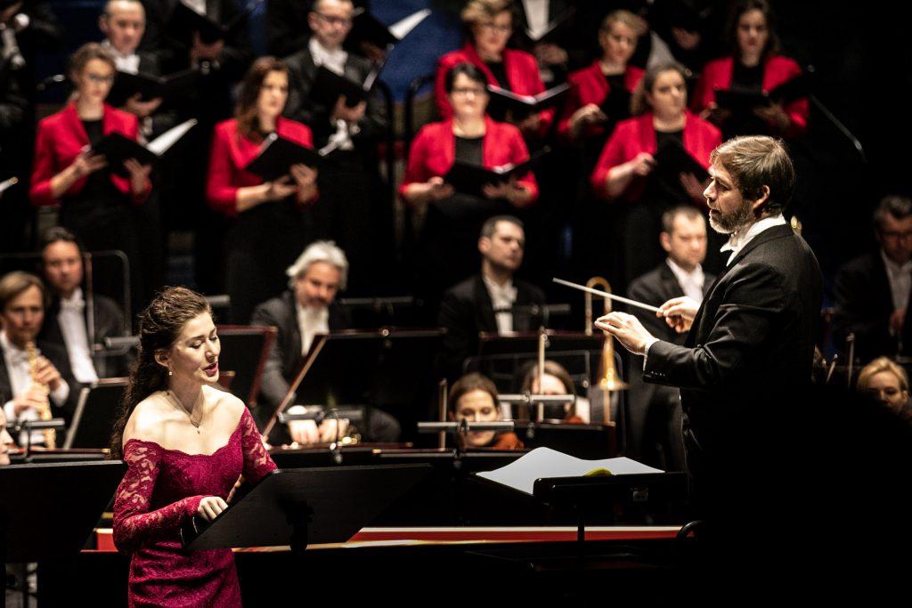 Po lewej stronie stoi solistka w długiej sukni. Po prawej stronie stoi dyrygent zwrócony w jej stronę. Za nimi widoczna część orkiestry i chóru.