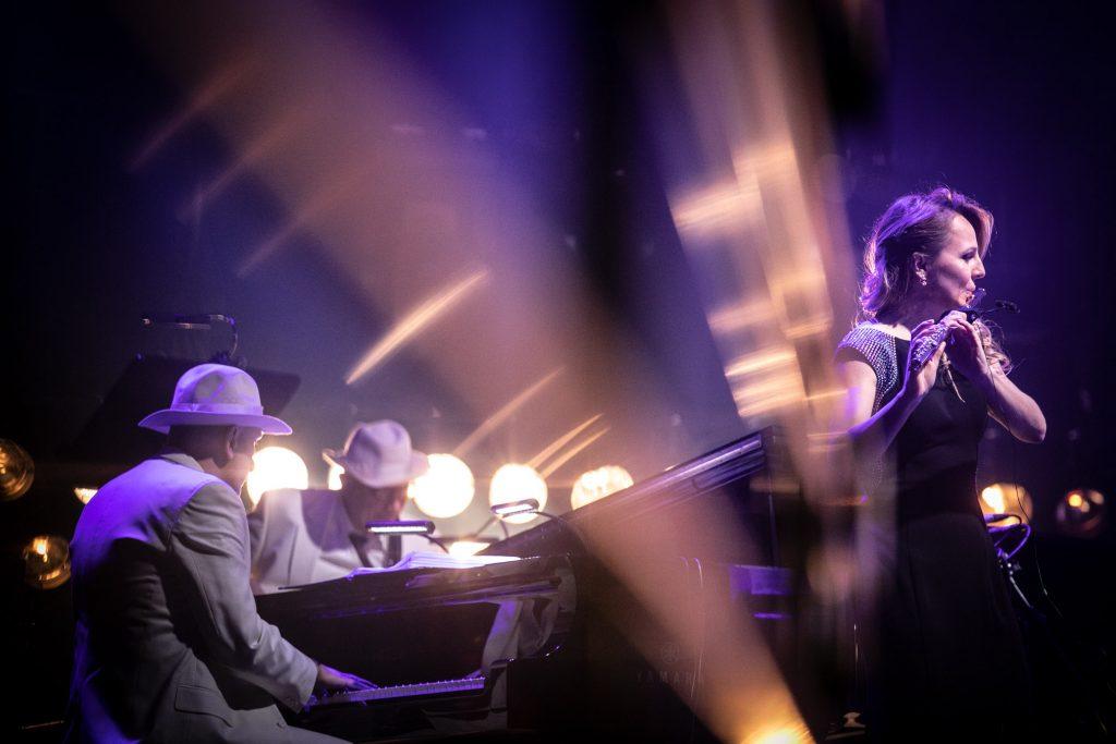Po lewej stronie kobieta w długiej sukni gra na flecie. Po lewej stronie przy fortepianie siedzi mężczyzna w białej marynarce i kapeluszu. Na zdjęciu widoczne smugi jasnego światła.
