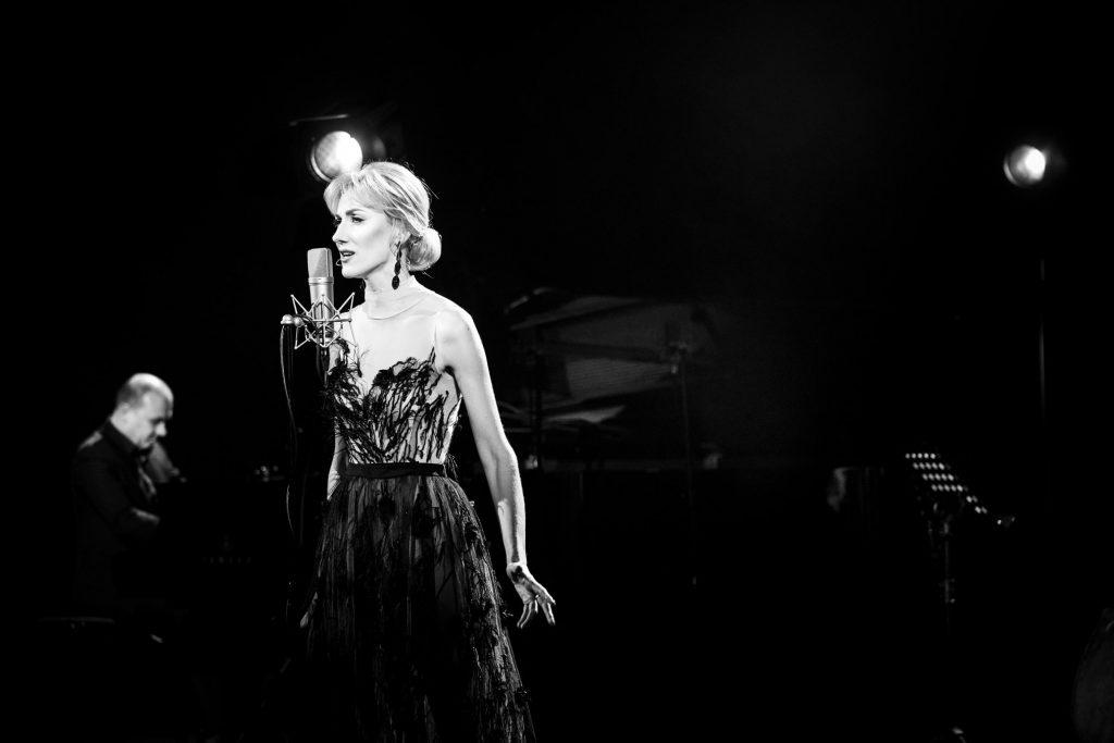 Czarno - białe zdjęcie. Na środku, przy mikrofonie stoi bokiem kobieta w długiej sukni. Za nią po lewej stronie siedzi mężczyzna przy fortepianie.