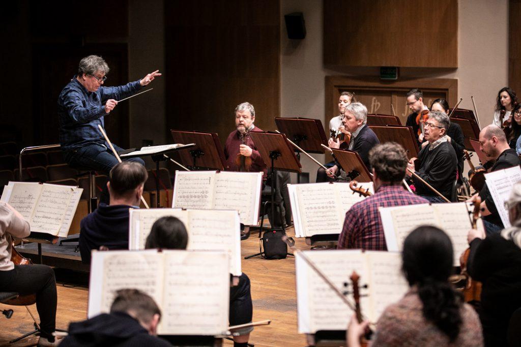 Grupa smyczkowa podczas próby do koncertu. W środku siedzi dyrygent - Prof. Jacek Błaszczyk.