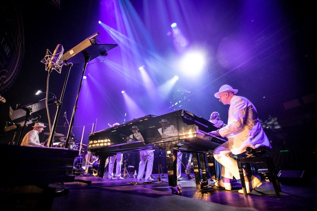 Widok z tyłu sceny. Po prawej stronie przy fortepianie siedzi mężczyzna w białej marynarce i kapeluszu. Za nim stoi część zespołu ''Big Band''. Z góry oświetla scenę kilka reflektorów.