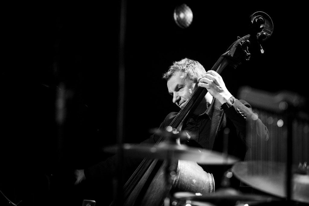 Czarno - białe zdjęcie. Z przodu widoczna część perkusji. Za nią mężczyzna grający na kontrabasie.