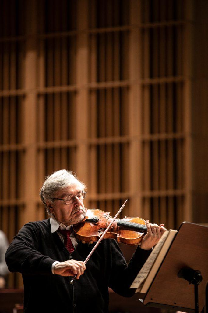 Na zdjęciu mężczyzna grający na skrzypcach.