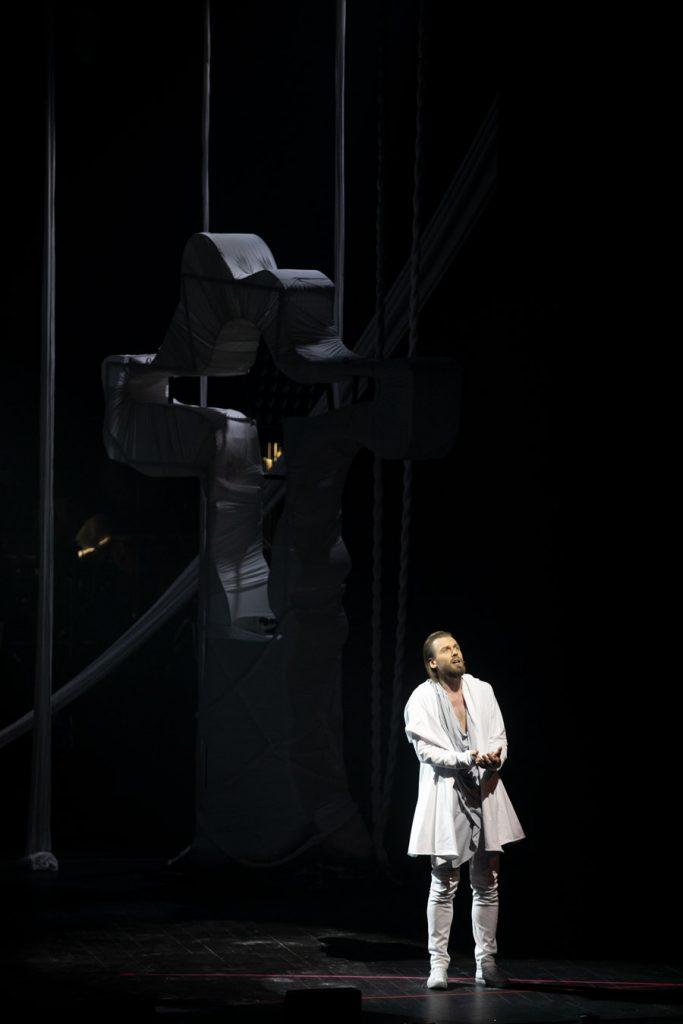 Na ciemnym tle sceny stoi mężczyzna ubrany na biało.