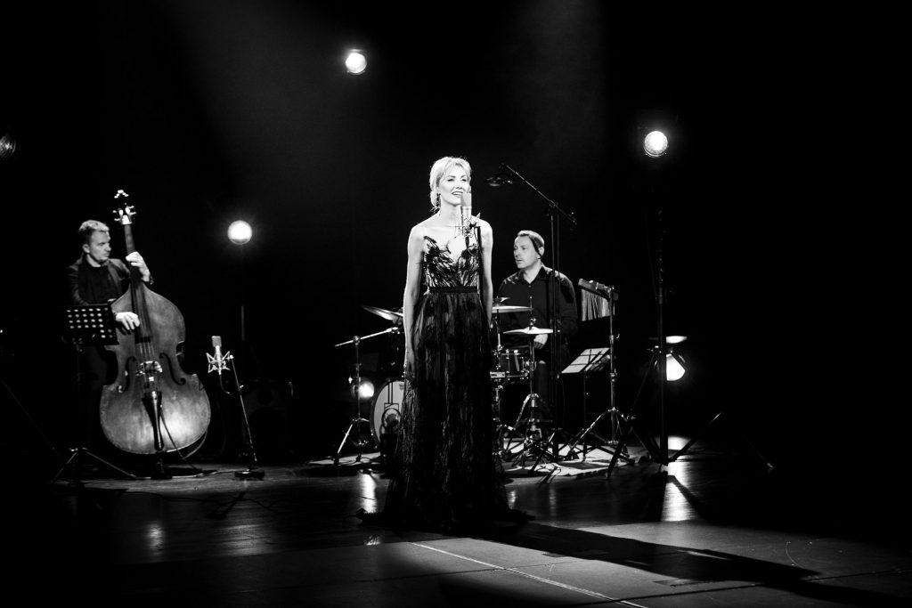 Zdjęcie czarno-białe. Na środku stoi kobieta w długiej sukni w smudze światła. Za nią po lewej stronie siedzi mężczyzna grający na kontrabasie. Po prawej stronie siedzi mężczyzna przy perkusji. Za nimi widoczne reflektory.