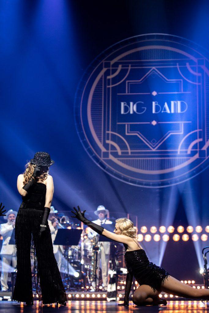 Scena oświetlona niebieskim światłem. Po prawej stronie siedzi na scenie kobieta w czarnej sukience z ręka wyciągniętą w stronę kobiety stojącej obok. Za nimi Big Band Opery i Filharmonii Podlaskiej. Na górze iluminacja świetlna z napisem Big Band.