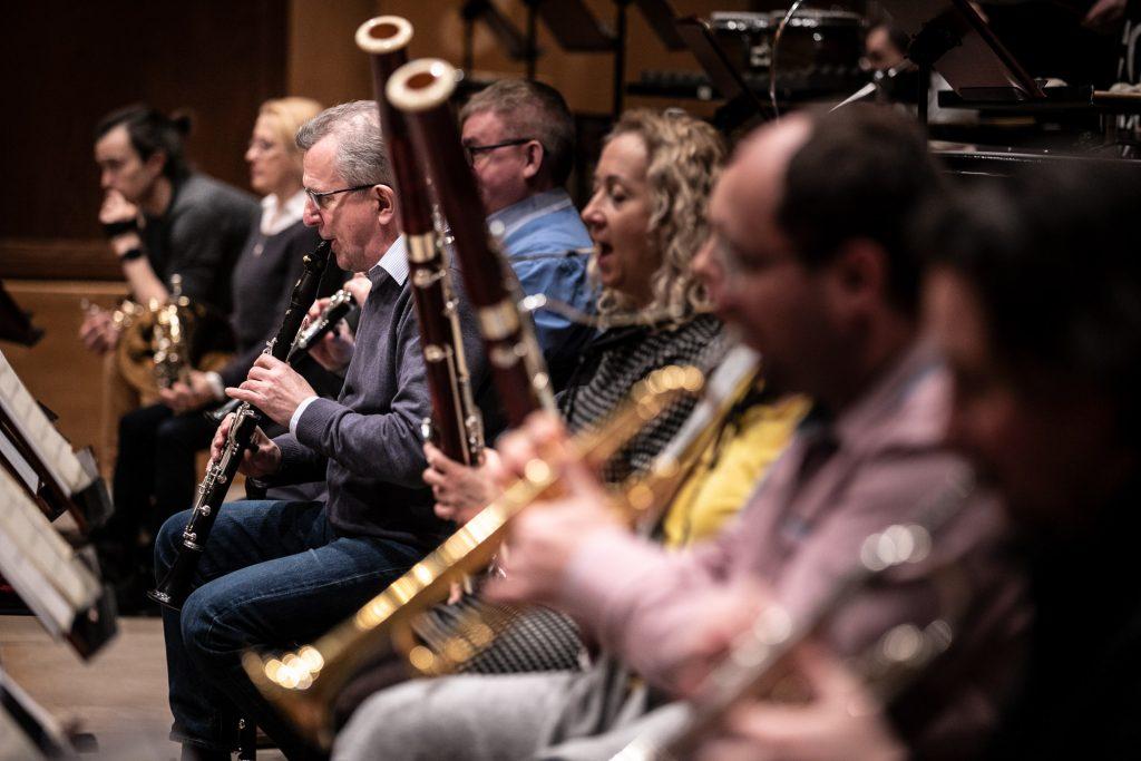 Ujęcie z boku. W rzędzie muzycy z sekcji dętej podczas próby do koncertu.