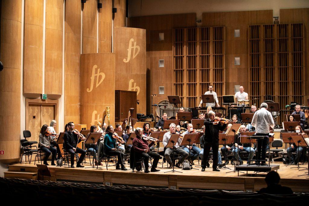 Próba do koncertu. Na środku stoi solista grający na skrzypcach. Za nim dookoła siedzi orkiestra. Obok na podeście stoi dyrygent.