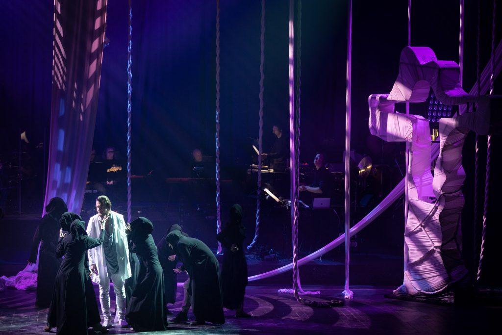 Scena oświetlona niebieskim światłem. Po lewej stronie stoi mężczyzna ubrany na biało. Wokół niego kilka postaci w czarnych pelerynach z kapturami na głowie. Z góry zwisają w kilku miejscach białe liny. Po prawej stronie stoi metalowy , wysoki krzyż, owinięty białym materiałem. Z tyłu widoczna orkiestra.