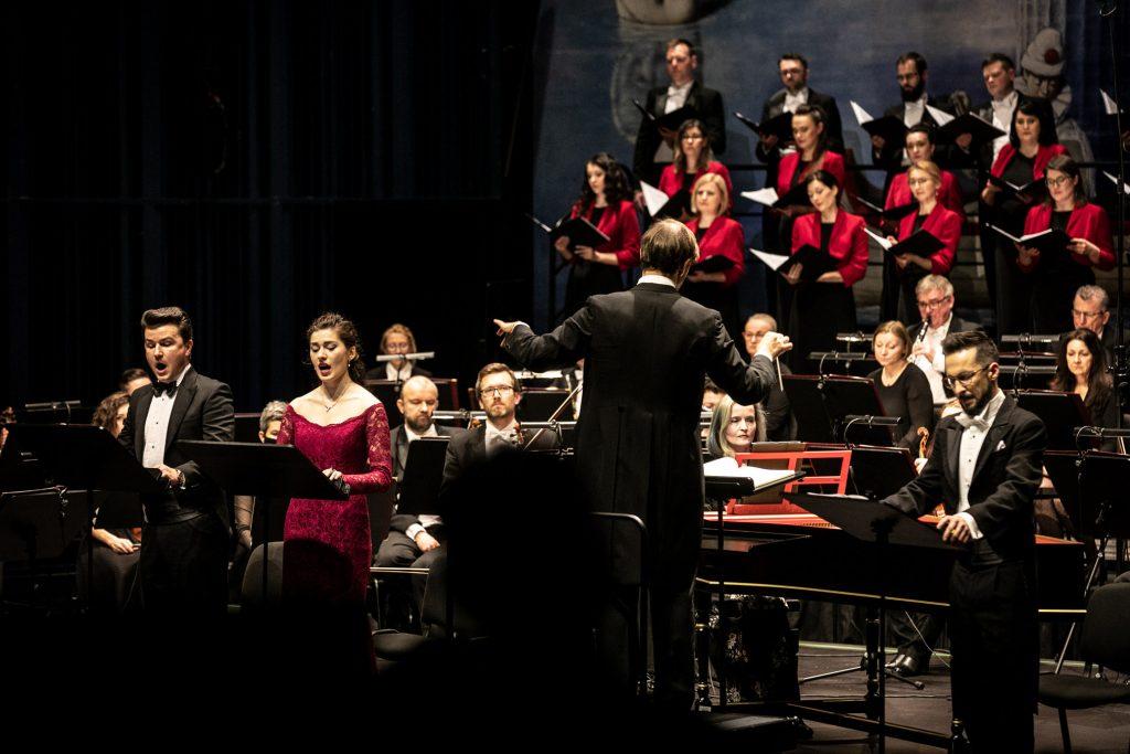 Na scenie soliści , część orkiestry i chóru mieszanego. Tyłem stoi dyrygent.