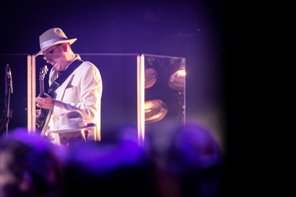 Scena w półmroku. Po lewej stronie mężczyzna w białej marynarce i kapeluszu gra na gitarze. Za nim stoi parawan akustyczny.