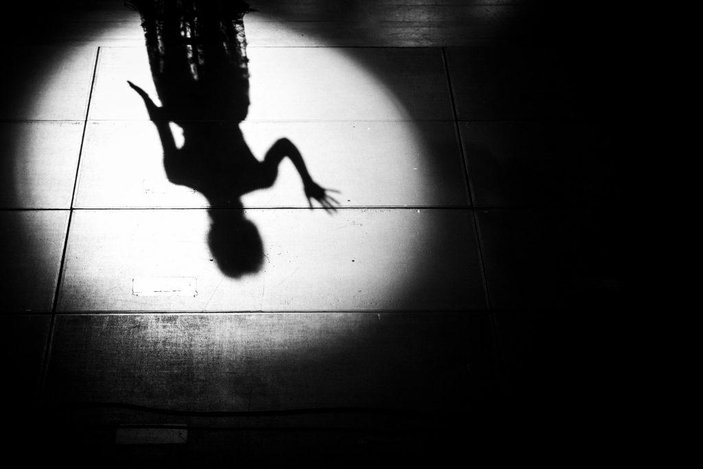 Na czarnym tle biały okrąg jasnego światła. W nim cień kobiety widoczny na wspak.