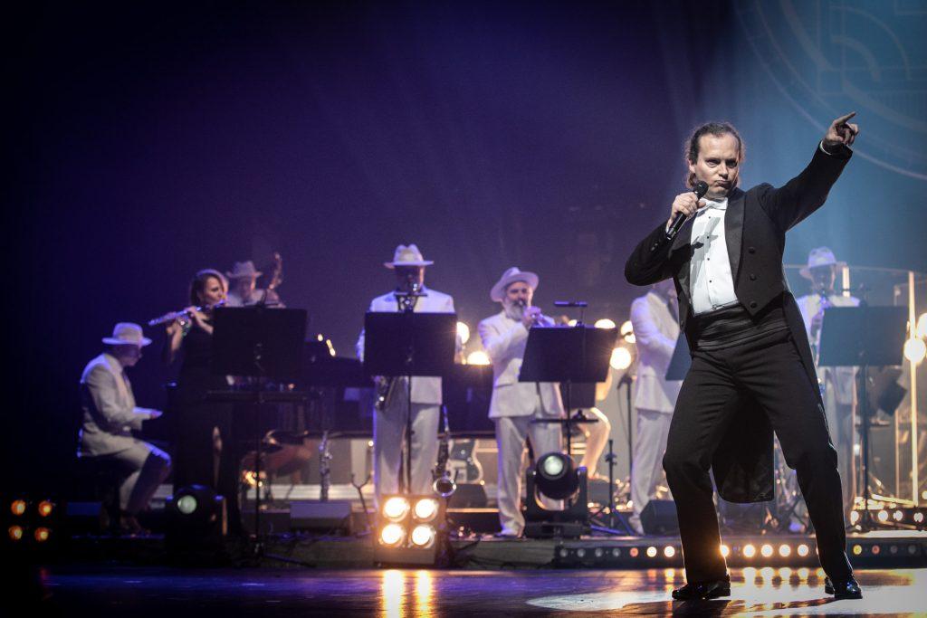 Po prawej stronie stoi mężczyzna w czarnym fraku i mikrofonem, z ręka wyciągniętą w bok. Za nim gra zespół Big Band Opery i Filharmonii Podlaskiej.