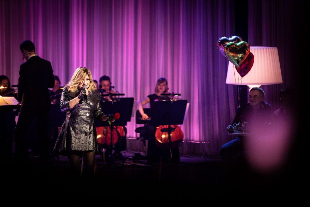 Scena oświetlona fioletowym światłem. Na niej z mikrofonem stoi artystka - Beata Kozidrak. Za nią widoczna część Orkiestry Tomasza Szymusia. Po prawej stronie siedzi mężczyzna trzymający balony w kształcie serc, za nim stoi duża, biała lampka.