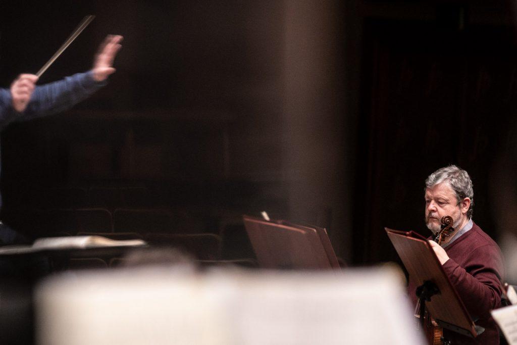 Przed jednym z pulpitów siedzi muzyk z sekcji smyczkowej.