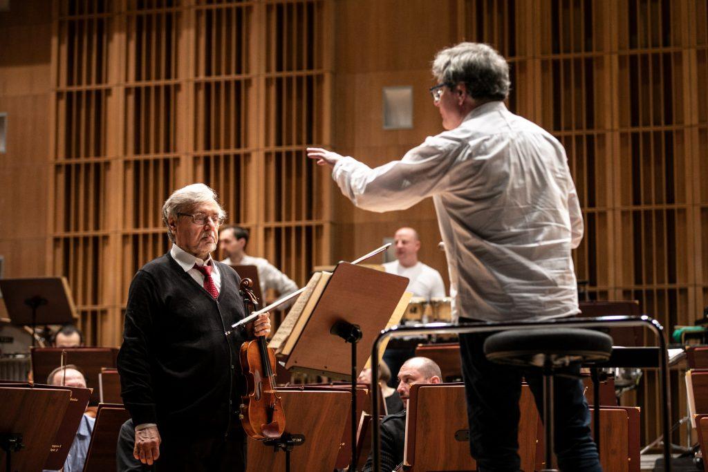 Na środku z uniesioną ręką stoi dyrygent. Po lewej stronie ze skrzypcami stoi solista. Za nimi widoczna część orkiestry.