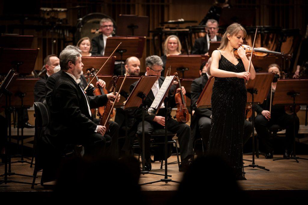 Solistka w czarnej, długiej sukni gra na skrzypcach. Dookoła niej siedzi orkiestra.