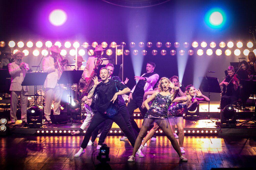 Scena oświetlona biało-różowym światłem. Na środku w pozycjach tanecznych stoi kilka kobiet i mężczyzn. Za nimi po prawej stronie widoczna część grupy smyczkowej. Po lewej stronie gra Big Band Opery i Filharmonii Podlaskiej.Z tyłu dwa rzędy reflektorów