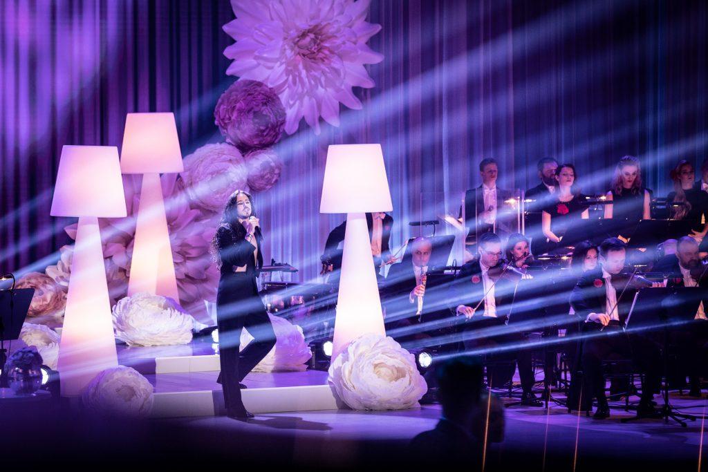 Scena podświetlona na niebiesko. Na środku stoi artysta - Michał Szpak z mikrofonem. Dookoła niego duże, białe lampki. Przed nimi leżą duże jasne róże. Po prawej stronie widoczna część Orkiestry Tomka Szymusia.
