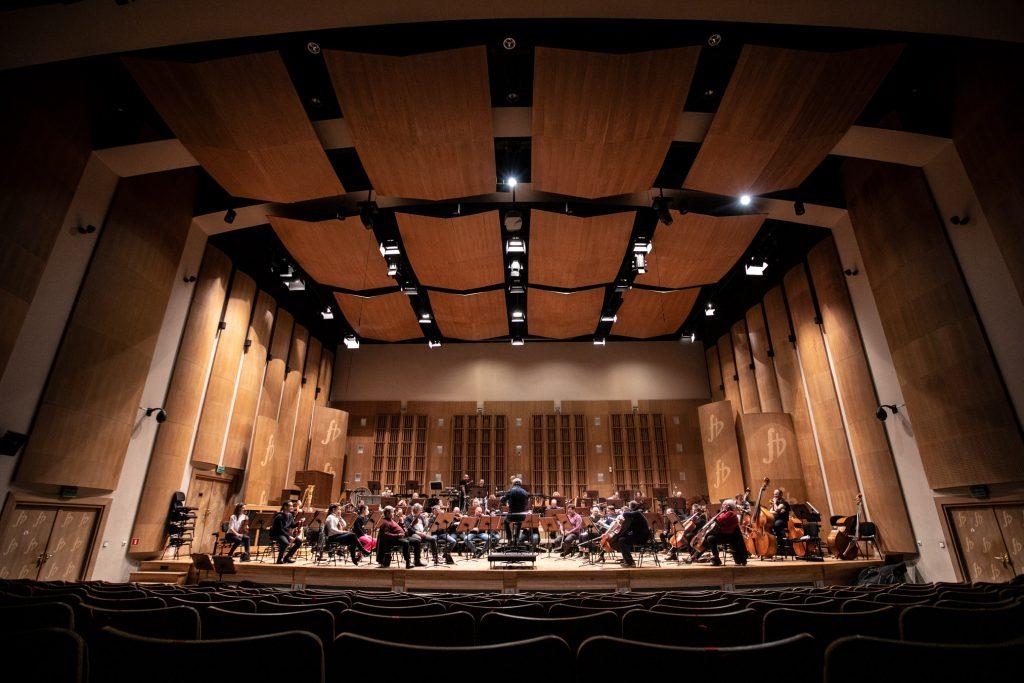 Zdjęcie z końca widowni. Na scenie orkiestra Opery i Filharmonii Podlaskiej podczas próby do koncertu.