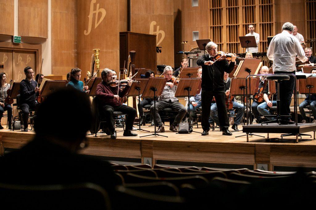 Z przodu na pustej widowni siedzi mężczyzna. Na scenie solista grający na skrzypcach, orkiestra i dyrygent podczas próby do koncertu.