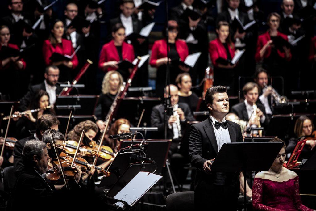 Na środku przed pulpitem stoi solista. Po lewej stronie widoczna część sekcji smyczkowej. Dalej siedzi grupa dęta. Na końcu stoi chór mieszany.