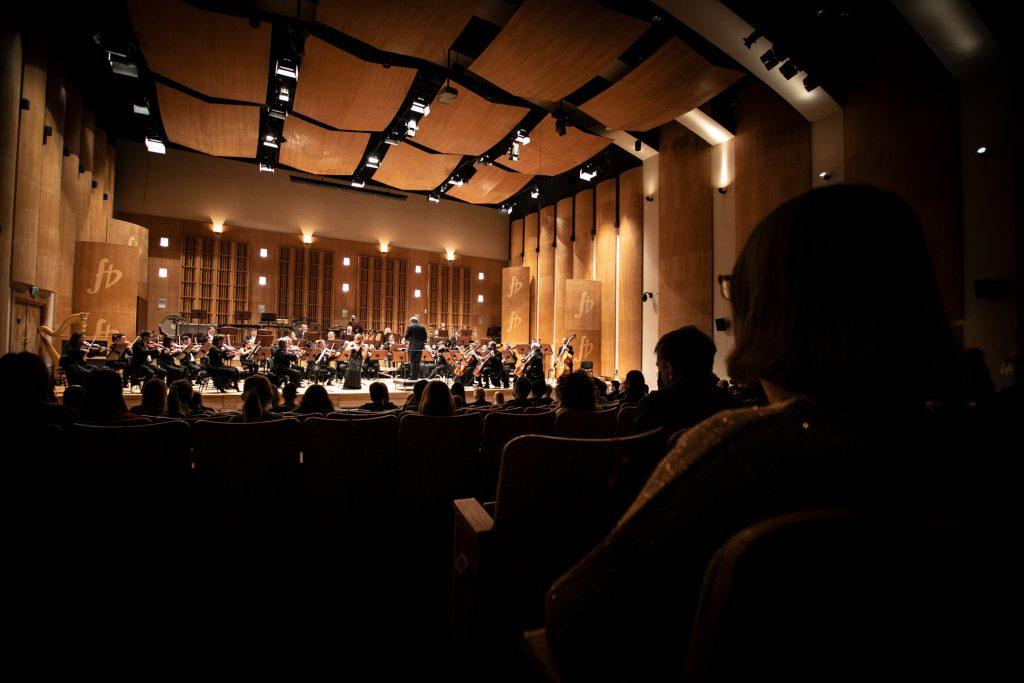 Widok z końca widowni. Publiczność widoczna tyłem. Na scenie orkiestra wraz z dyrygentem. Na środku stoi solistka w czarnej, długiej sukni.
