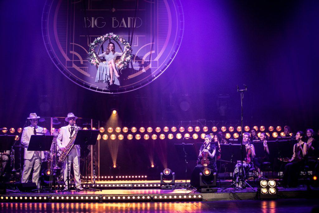 Na scenie po prawej stronie siedzi sekcja smyczkowa. Po lewej stronie stoi dwóch mężczyzn w białych garniturach z instrumentami dętymi. Na górze, na podwieszonej huśtawce siedzi kobieta w długiej sukni. Na scenie w kilku miejscach rzędy świateł.