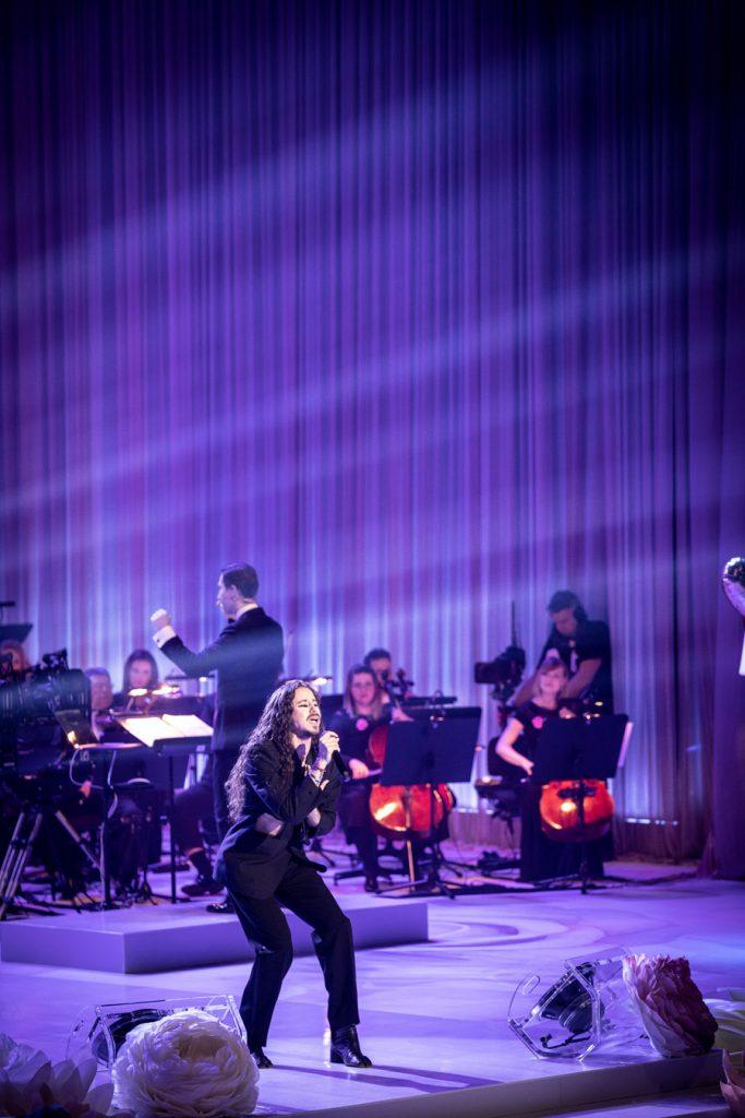 Scena oświetlona niebieskim światłem. Na środku z mikrofonem stoi Michał Szpak. Za nim widoczna część Orkiestry Tomka Szymusia.