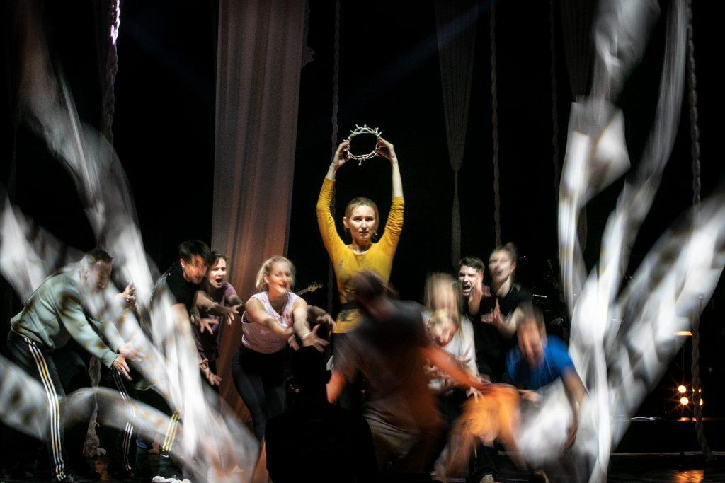 Na środku stoi kobieta trzymając nad głową koronę cierniową. Wokół niej tancerze z wyciągniętymi rękami.