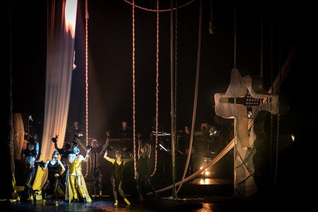 Scena w półmroku. Po prawej stronie stoi metalowy, wysoki krzyż, owinięty białym materiałem. Po lewej stronie grupa tancerzy w czarnych kostiumach i pióropuszach. Na środku stoi mężczyzna w złotym garniturze z mikrofonem. Z góry wiszą białe liny. Za nimi na podwyższeniu siedzi orkiestra.