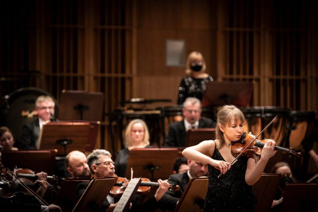 Solistka w czarnej sukni podczas wykonywania utworu. Za nią siedzi orkiestra.