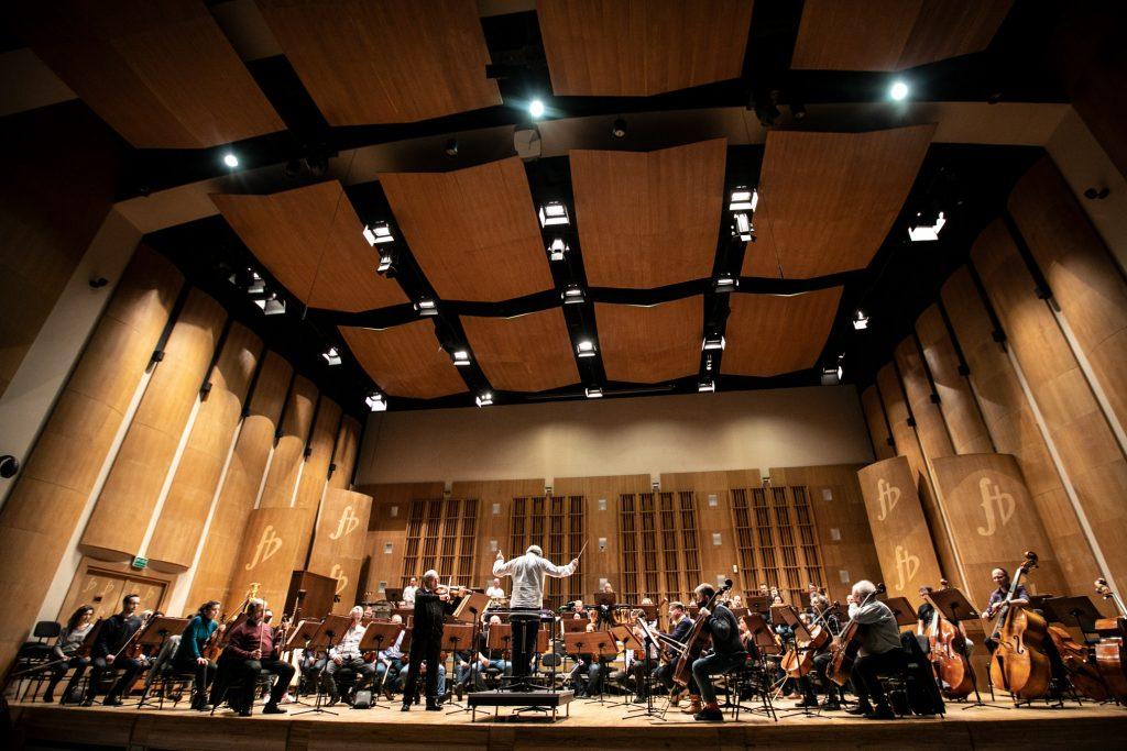 Na scenie orkiestra wraz z dyrygentem oraz solista podczas próby do koncertu.