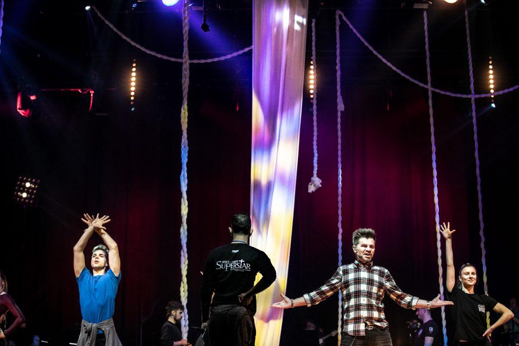 Mężczyzna w koszuli w kratkę trzyma rozłożone ręce na boki. Po lewej stronie stoi mężczyzna z rękami skrzyżowanymi nad głową. Przed nimi tyłem stoi mężczyzna w czarnej bluzce z napisem Jesus Christ Superstar. Za nimi wiszą białe liny.