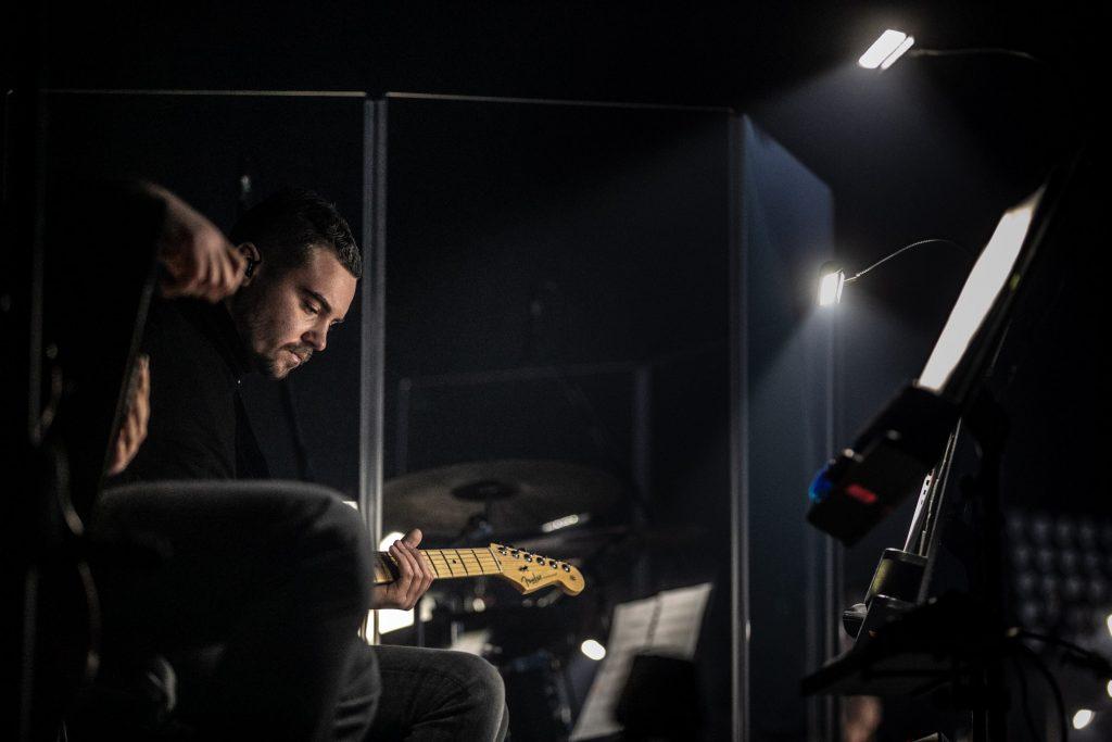 Na zdjęciu mężczyzna grający na gitarze elektrycznej.