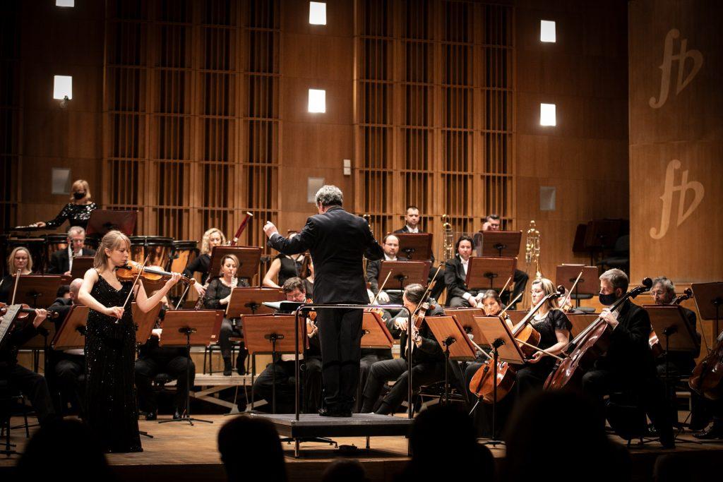 Po lewej stronie stoi solistka grająca na skrzypcach. Po prawej stronie stoi dyrygent. Za nimi siedzi orkiestra.