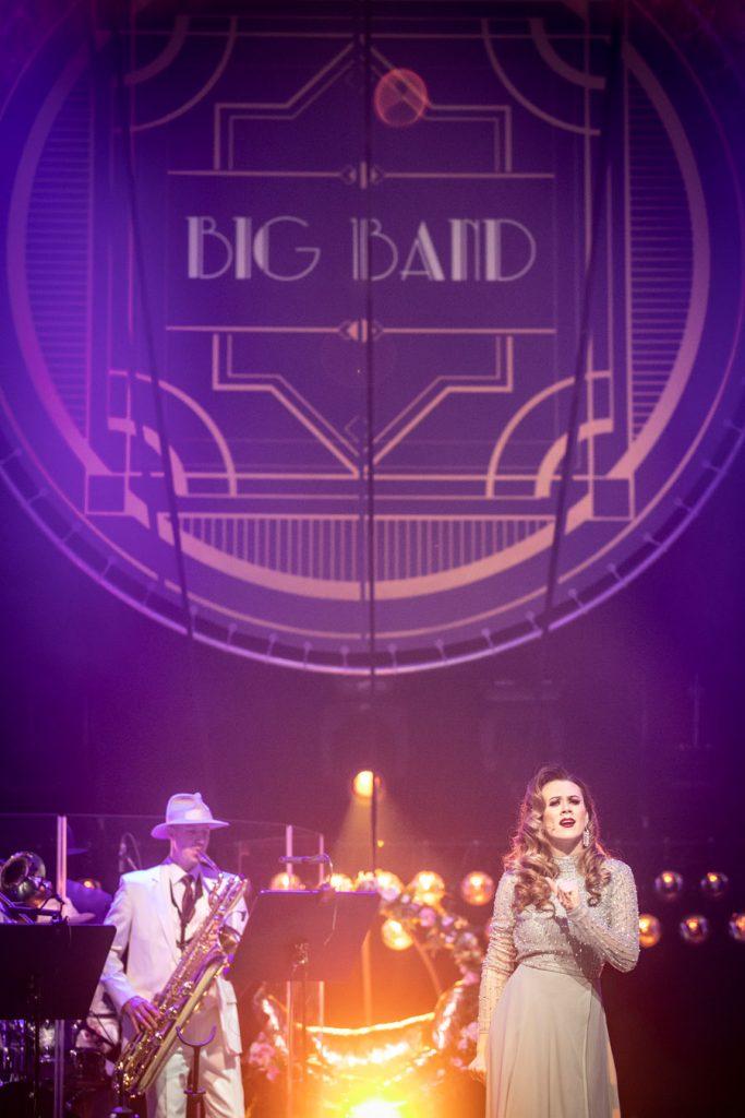 Na scenie kobieta w długiej sukni, za nią po lewej stronie mężczyzna grający na saksofonie. Pomiędzy nimi widoczna huśtawka ozdobiona kwiatami. Na górze widoczna iluminacja z napisem ''Big Band''.