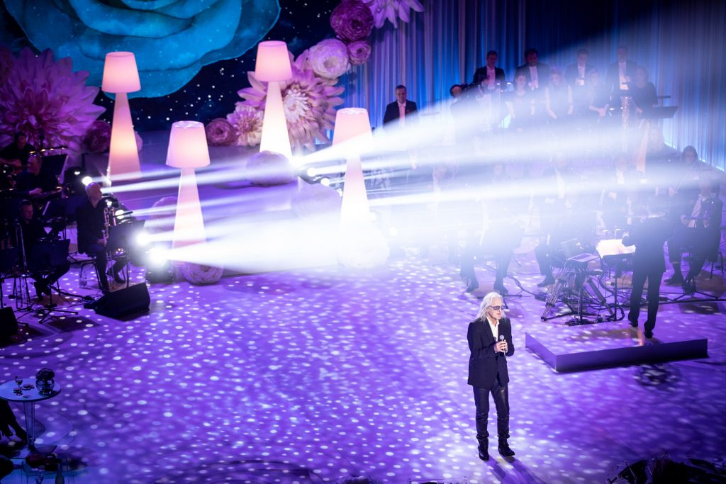 Scena oświetlona na niebiesko. Z przodu stoi artysta - Grzegorz Markowski. Za nim widoczne schody i podświetlone duże, białe lampki. Z ich boku widoczne smugi jasnego światła. Po obydwu stronach siedzi Orkiestra Tomka Szymusia.