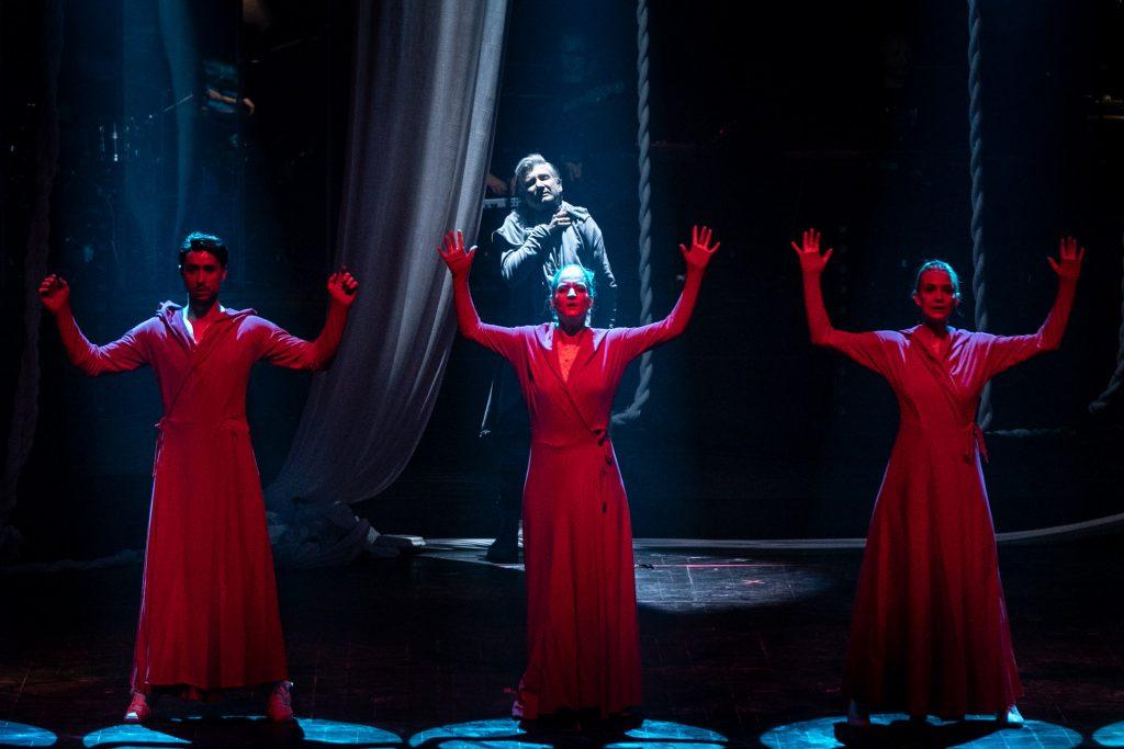 Trójka tancerzu w czerwonych płaszczach stoi w rzędzie z podniesionymi do góry rękoma. Za nimi stoi mężczyzna. Wokół niego wiszą białe liny.
