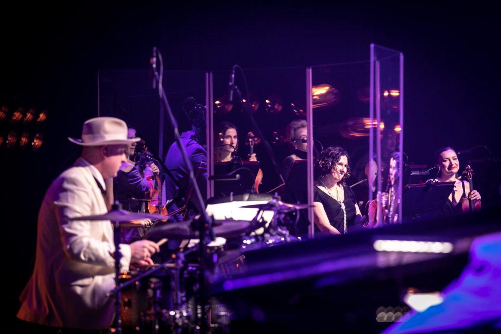 Zbliżenie na mężczyznę grającego na perkusji, przed nim widoczny parawan akustyczny. Za nim siedzi sekcja smyczkowa.