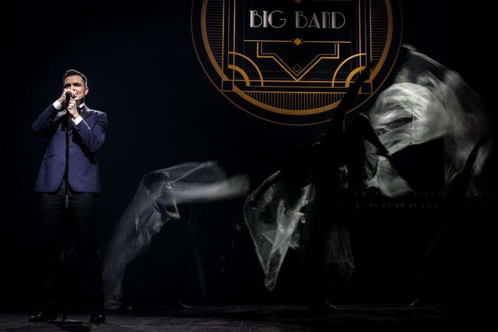 Na środku sceny w półmroku tańczy kilku tancerzy z delikatnymi woalami podświetlonymi smugami światła. Po lewej stronie na czarnym tle stoi mężczyzna przy mikrofonie. Z tyłu iluminacja świetlna z napisem BIG BAND.