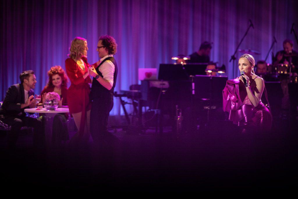 Na scenie po prawej stronie stoi z mikrofonem piosenkarka Ania Wyszkoni. Po lewej stronie kobieta w czerwonej sukience i mężczyzna tańczą ze sobą. Za nimi przy stoliku siedzi para. Po prawej stronie część muzyków orkiestry.