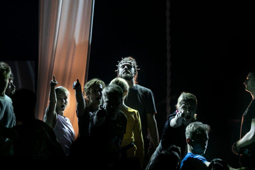 Mężczyzna stoi na środku sceny z koroną cierniową na głowie. Wokół niego kilkanaście osób z rękami wyciągniętymi przed siebie.