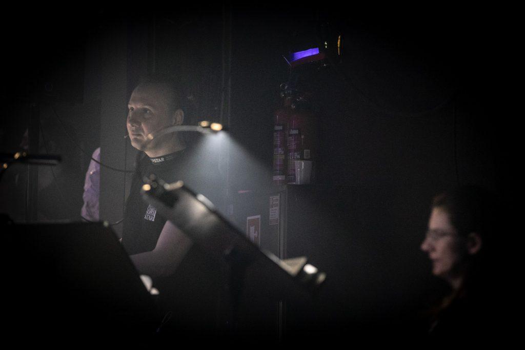 Na zdjęciu widoczny mężczyzna w koszulce z napisem Jesus Christ Superstar patrżący przed siebie. Przed nim podświetlony pulpit.