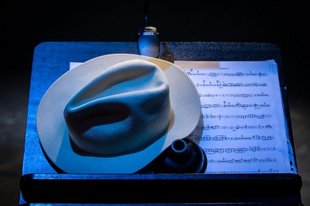 Zbliżenie na pulpit do nut na którym leży partytura, na niej- jasny kapelusz.