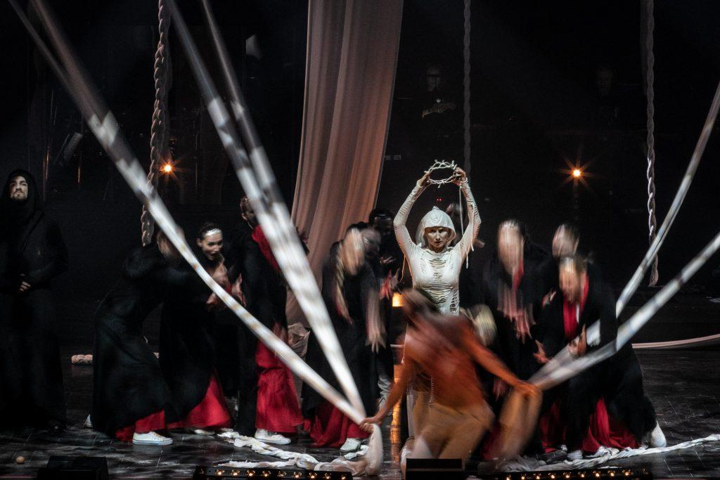 Na scenie na środku klęczy mężczyzna. W dłoniach trzyma zwoje białego materiału wiszącego z góry. Za nim stoi kobieta ubrana w biały kostium, trzyma w podniesionych rękach koronę cierniową. Za nimi dookoła stoją tancerze z wyciągniętymi rękoma w czarnych płaszczach.