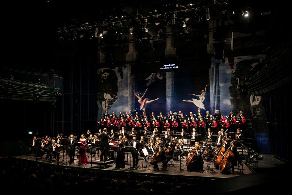 Zdjęcie z końca widowni na scenę podczas koncertu ''Stworzenie świata''. Na niej Orkiestra i Chór Oifp. Z przodu przed pulpitami stoją soliści , pomiędzy nimi na podeście stoi dyrygent.