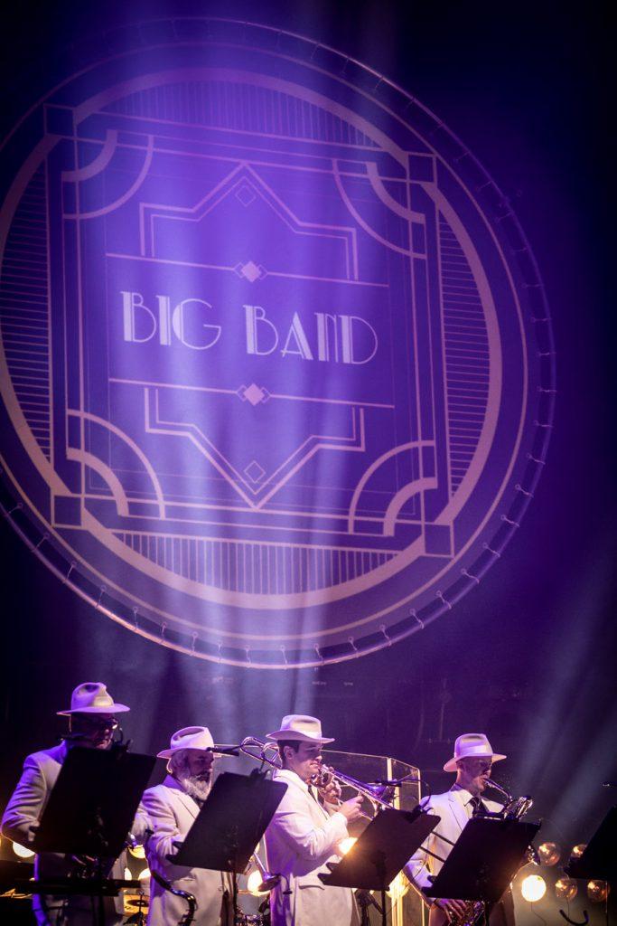 Na środku iluminacja przedstawiająca nazwę zespołu ''Big Band''. Na dole zdjęcia czterech mężczyzn w białych garniturach grających na instrumentach dętych.