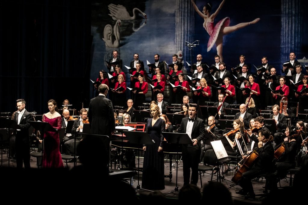 Na scenie Chór i Orkiestra Opery i Filharmonii Podlaskiej. Z przodu, przed pulpitami stoją soliści, przed nimi na podeście stoi dyrygent.